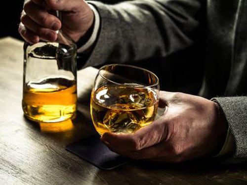 Мужчина держит стакан с виски