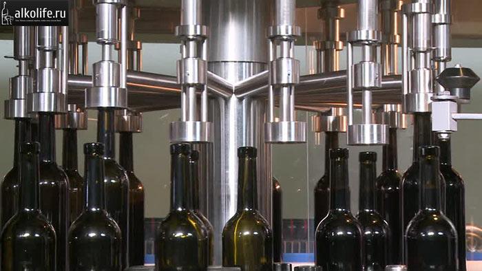 Укупорка бутылок с вином на заводе